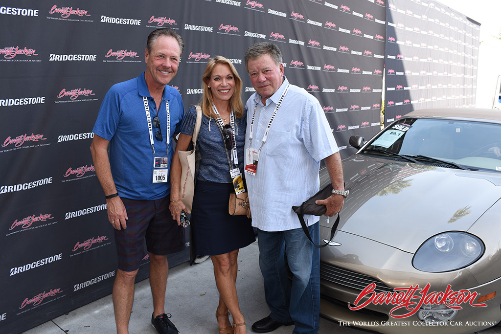 Legendary actor William Shatner poses with the winning bidders on his 2002 Aston Martin DB7, which he autographed for the couple.