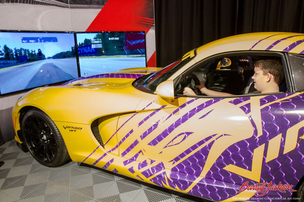 A young driver-in-the-making checks out a Dodge Viper simulator in the Sponsor Pavilion.