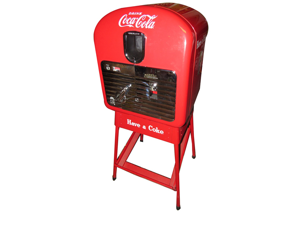 Back in the 1940s, you and your date would have sauntered up to a soda machine just like this one to get your Coca-Cola! Nearly impossible to find in this day-one condition, this Vendo 27 coin-operated soda machine (Lot #5975) featured chrome-plated access doors and is on its original stand.