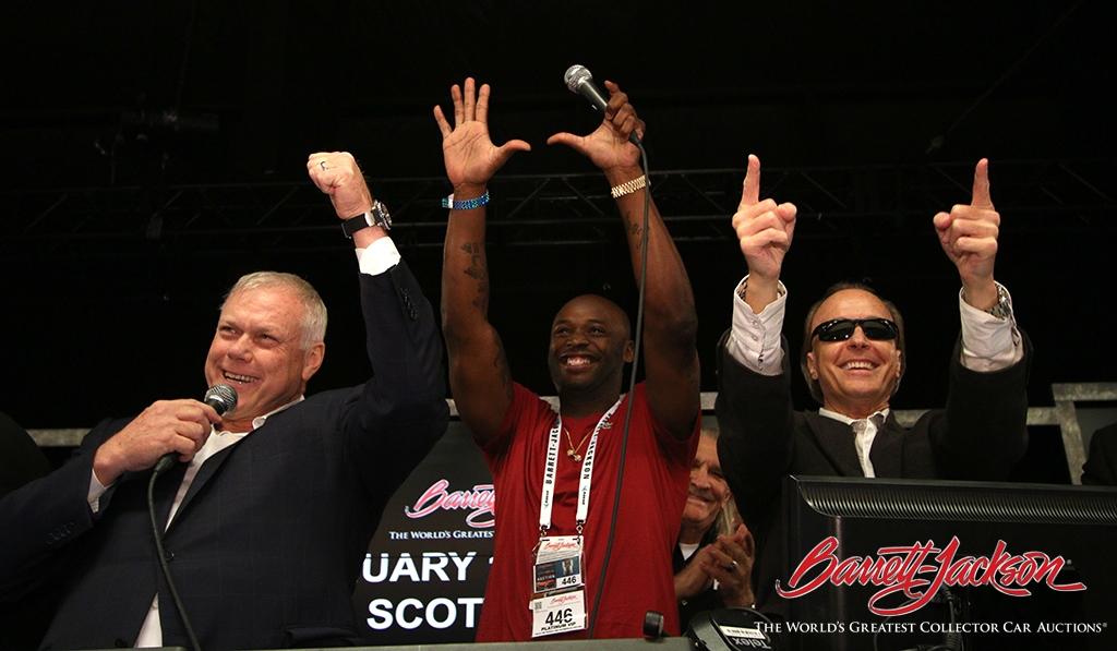 Barrett-Jackson Chairman and CEO Craig Jackson, NFL wide receiver Reggie Wayne and Barrett-Jackson President Steve Davis celebrate the Top 10 sale of Wayne's 1967 Ford Mustang GT Custom Fastback (Lot #707) at today's auction.