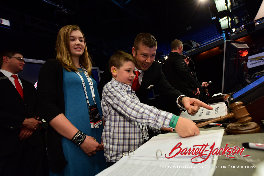 Lead auctioneer Joseph Mast shows the ropes to his son Micah and daughter Emma.