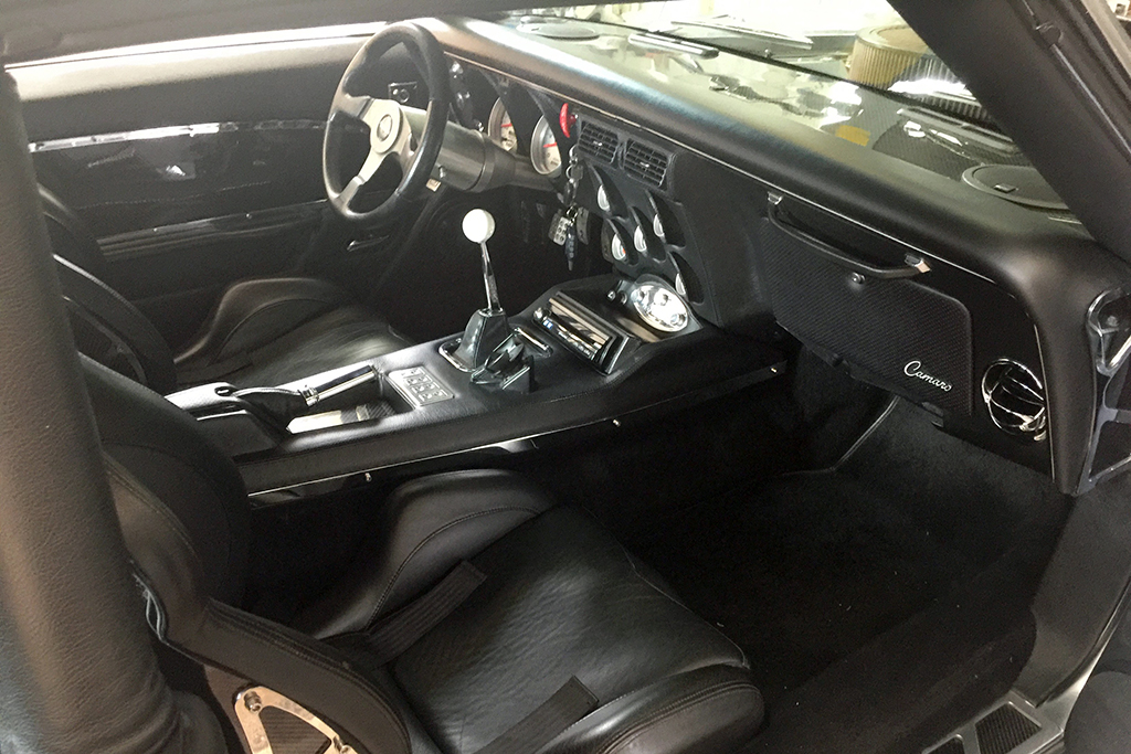 The black leather interior of the '68 Camaro features Cobra seats, Corbeau belts, and custom carbon-fiber door panels and trim.