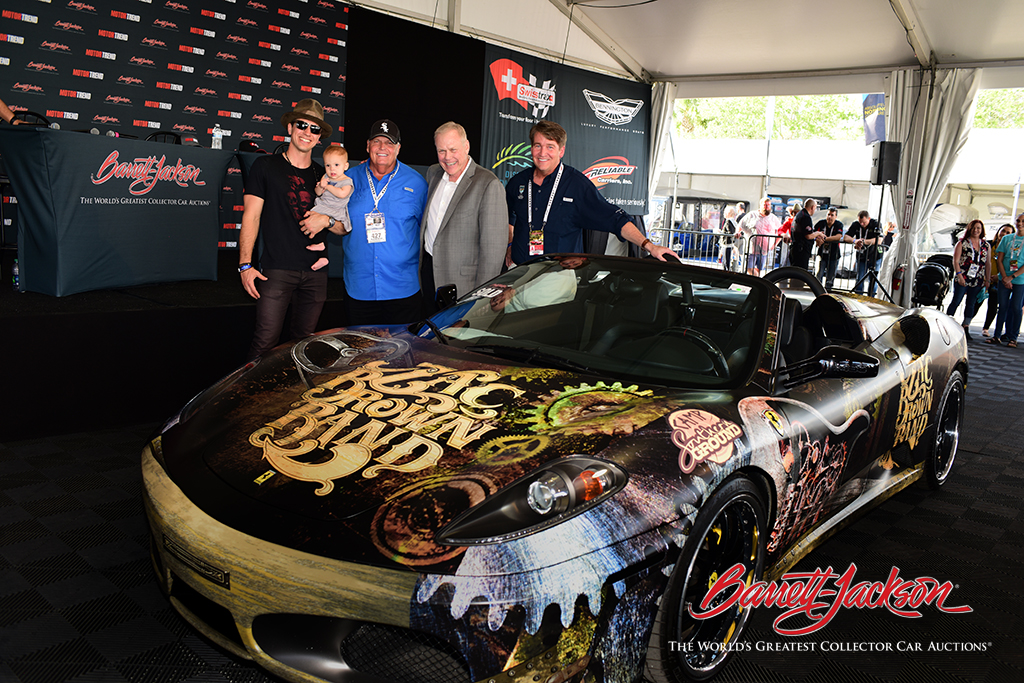 From left: Zac Brown Band fiddler Jimmy De Martini with one of his children, winning bidder Rick Hendrick, Craig Jackson, and Camp Southern Ground CEO Mike Dobbs with the Zac Brown Band Ferrari.