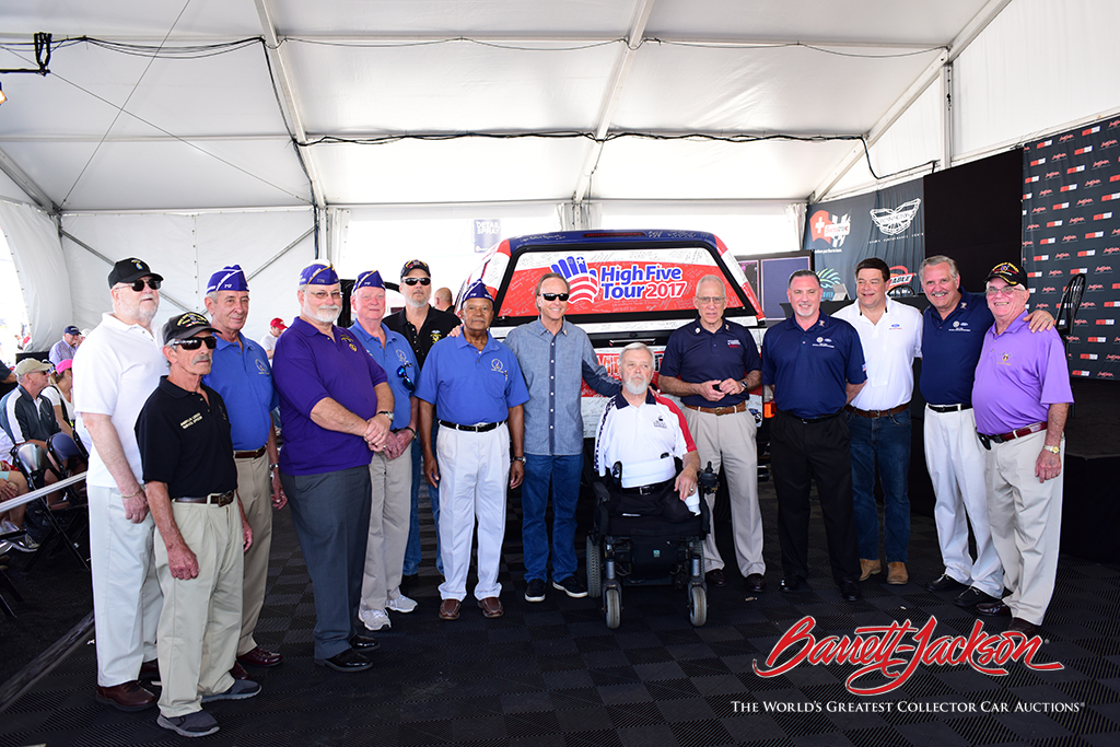 Purple Heart recipient, retired Army Captain Tommy Clack (center), with Barrett-Jackson President Steve Davis, Founder and President of Wounded Warriors Family Support Colonel John Folsom, UAW-Ford National Veterans Department Assistant Director David Berry, Ford Performance Marketing Manager Jim Owens and fellow Purple Heart recipients after Clack was presented with his new Ford F-250 pickup.