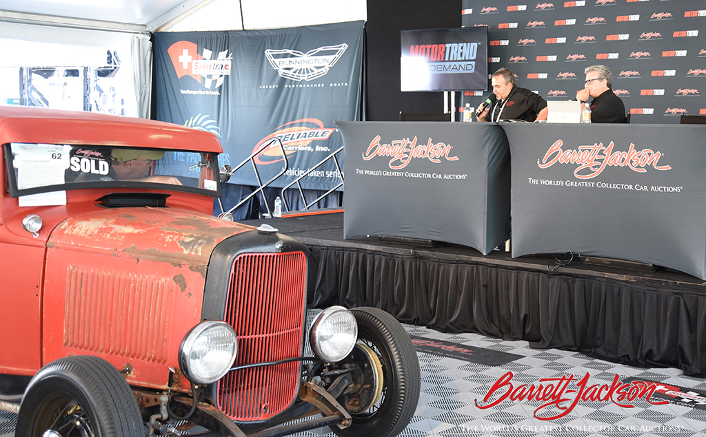 Craig Gussert and Alan Taylor discuss a 1932 Ford Custom Pickup (Lot #62) after its sale on Thursday.