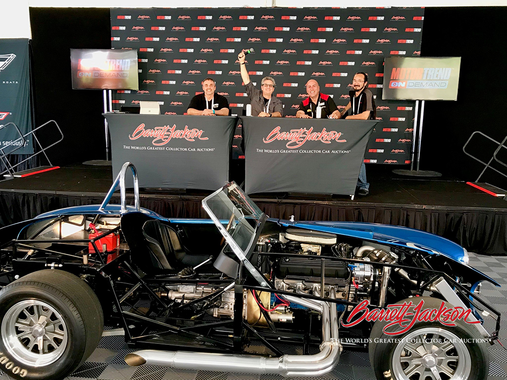 "Craig Gussert and Alan Taylor with Barrett-Jackson's Showroom Division Manager Jeff Catlin and Digital Media Manager Tim Heit, in front of a ""cutaway"" Cobra brought to the live stage to show the audience the inner workings of a car."